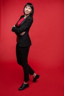 ズボンとオックスフォードシューズでエレガントな黒のスーツを着ている魅力的な笑顔の実業家のスタジオポートレート。彼女は赤い背景に対して腕を組んで保持しています。