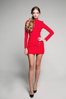 Студийный портрет привлекательной женщины с длинными волнистыми волосами в хвосте, носить мини-красное платье и черные высокие каблуки на белом фоне. изолировать.
