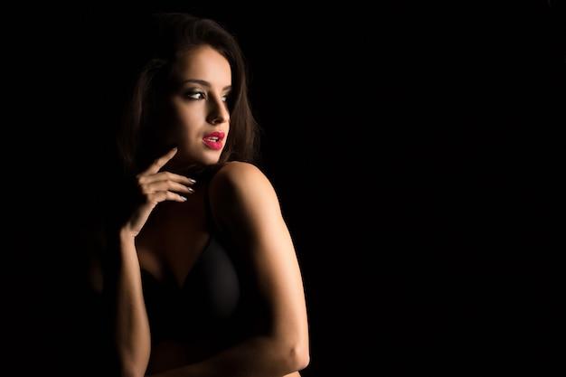 影の中で裸の肩でポーズをとって明るいメイクで魅力的な若い女性のスタジオポートレート