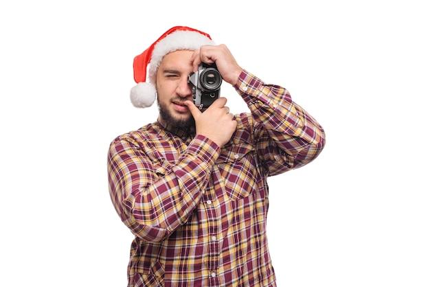 レトロなカメラを持ってサンタの帽子をかぶって写真を撮るひげを生やした男のスタジオポートレート。孤立した白い背景