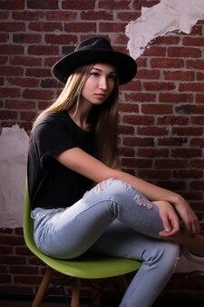 美しいブルネットモデルのスタジオポートレートは、レンガの壁の背景に帽子、tシャツ、破れたジーンズを着ています