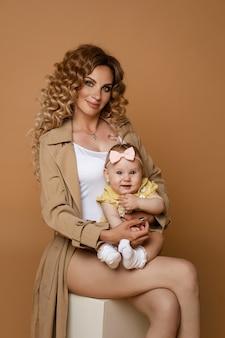 베이지 색 클래식 트렌치와 복숭아 벽에 흰색에 앉아 팔에 귀여운 아기 딸을 들고 흰색 탑을 입고 긴 물결 모양의 머리를 가진 아름 다운 백인 어머니의 스튜디오 초상화.
