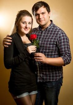 Студийный портрет красивой влюбленной пары, обнимающейся и смотрящей на фронт