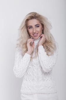 흰색 배경에 뜨거운 스웨터에 아름다운 긴 머리 금발 여자의 스튜디오 초상화