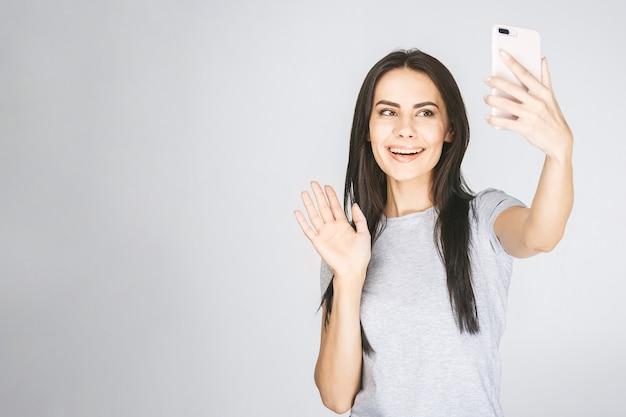 Портрет студии красивой женщины усмехаясь с белыми зубами и делая selfie, фотографируя над белой предпосылкой.