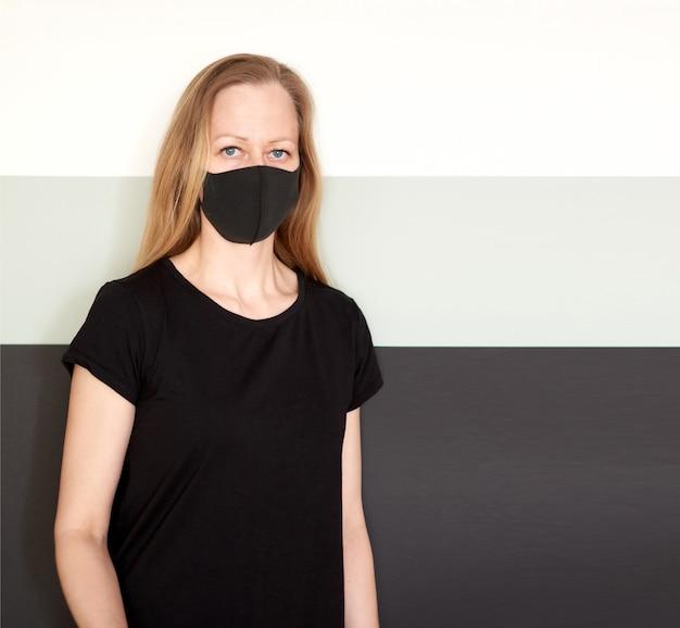コロナウイルスの流行中に保護するためのフェイスマスクの金髪女性のスタジオポートレート。