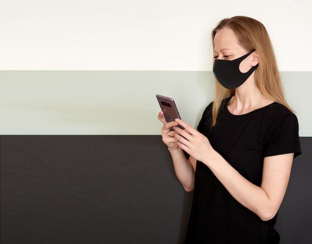コロナウイルスの流行中に保護するための電話とフェイスマスクで金髪の女性のスタジオポートレート。