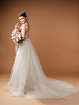 緑豊かなブライダルブーケとウェディングドレスのブルネットの花嫁のスタジオポートレート。