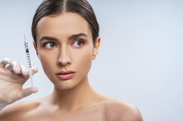 フィラーと注射器を保持している魅力的な若いきれいな新鮮な顔の美しいブルネットの女性のスタジオポートレート