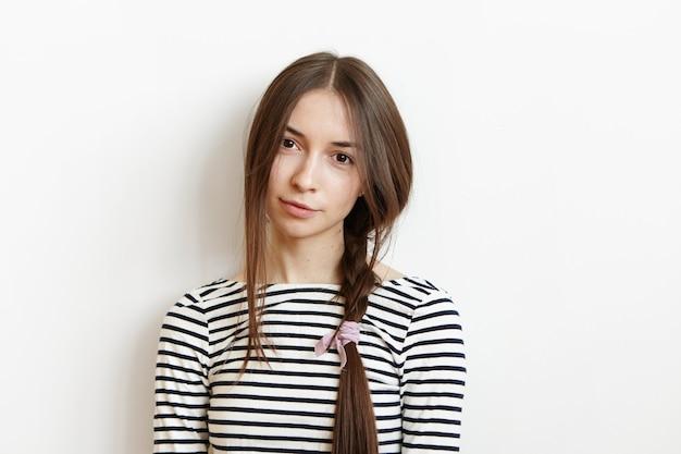 ストライプのトップを着て魅力的な若いヨーロッパのブルネットの女性のスタジオポートレート