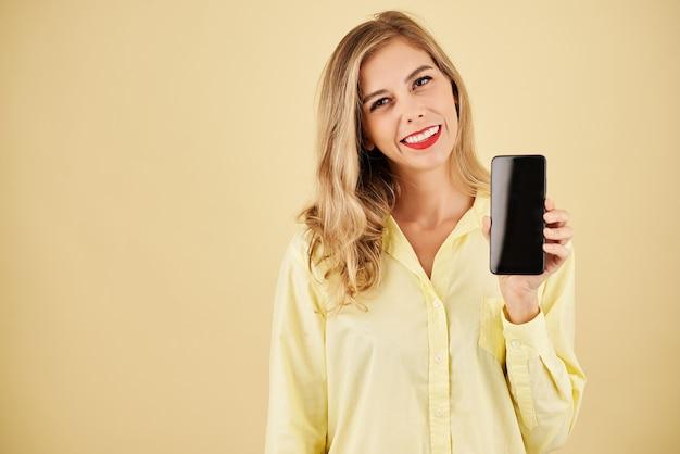 Студийный портрет веселой блондинки, показывающей новую модель смартфона
