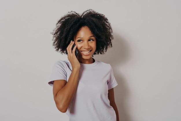 Студийный портрет веселой темнокожей женщины, наслаждающейся разговором по мобильному телефону, держащей смартфон на улыбке, слушая хорошие новости от друга, стоя изолированно на белом фоне