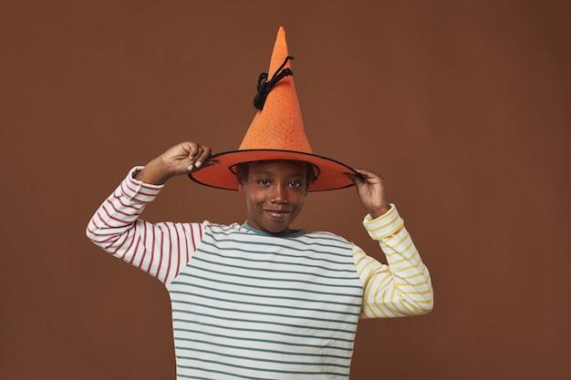 재미 있은 오렌지 마법사 모자에 노력하는 갈색 벽 표면에 서 쾌활한 어린 소년의 스튜디오 초상화