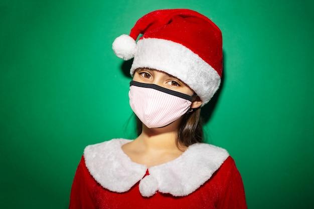 녹색 표면에 빨간 모자와 의료 얼굴 마스크를 착용하는 산타 의상 자식 소녀의 스튜디오 초상화