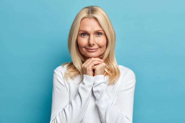 自信を持って50歳の女性のスタジオポートレートは、あごの下に手を置いて、落ち着いた表情でカメラを直接見ています白いセーターを着て、肌のポーズをよく気にしています
