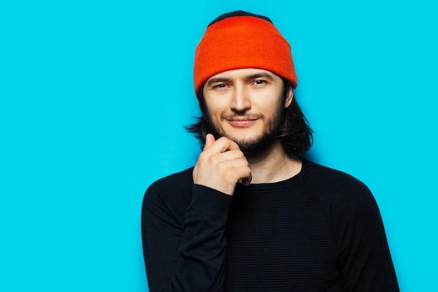青い背景にオレンジ色の帽子と黒のセーターを着ている自信を持って若い男のスタジオの肖像画。