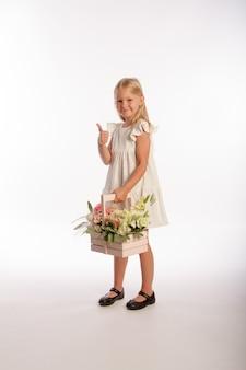 Студийный портрет милой блондинки в белом платье с деревянной корзиной цветов