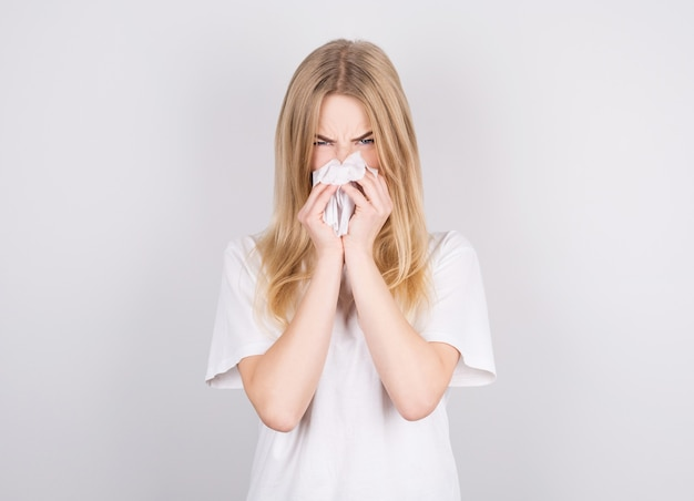 アレルギー、インフルエンザまたは風邪のためにくしゃみをする紙ナプキンを持つかわいい不健康な白人女性のスタジオポートレート