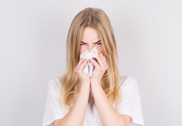 Студийный портрет симпатичной нездоровой кавказской женщины с бумажной салфеткой, чихающей из-за аллергии, гриппа или простуды