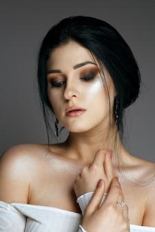 輝く肌と裸の肩を持つエレガントなブルネットの女性のスタジオポートレート。スタジオは灰色の背景の上で撮影しました