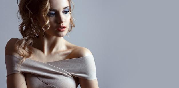 巻き毛と裸の肩を持つエレガントな若い女性のスタジオポートレート。テキスト用のスペース