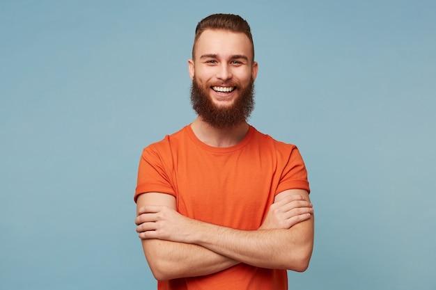 Студийный портрет эмоционального счастливого смешно улыбающегося парня с густой бородой стоит со скрещенными руками, одетого в красную футболку, изолированную на синем