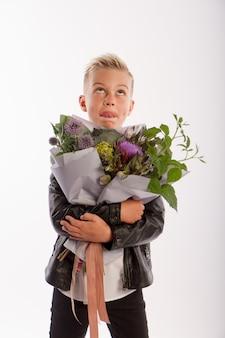 Студийный портрет модного белокурого кавказского мальчика с подарочным букетом