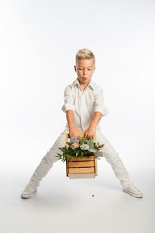Студийный портрет модного белокурого кавказского мальчика с деревянной корзиной цветов, белый фон, копией пространства