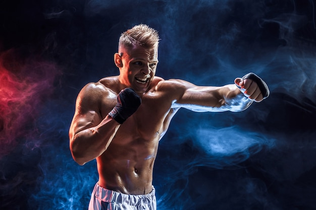 暗闇の中で煙の中で筋肉の男と戦うスタジオポートレート