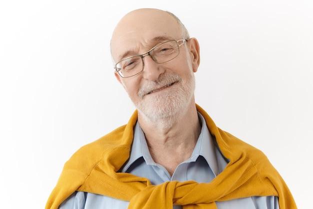 Студийный портрет дружелюбно выглядящего довольного зрелого семидесятилетнего небритого дедушки в прямоугольных очках и стильном свитере поверх рубашки, широко улыбающегося, счастливого видеть своих внуков