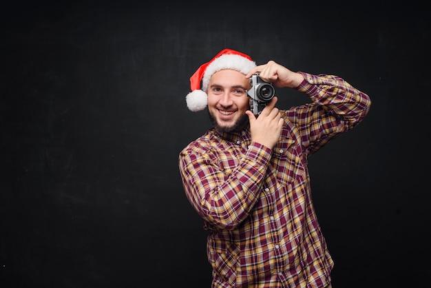 レトロなカメラを持ってサンタの帽子をかぶって写真を作っている、面白くて驚いたひげを生やした男のスタジオポートレート。テキスト用のスペース。ブラック