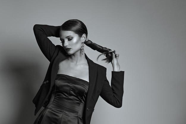 光沢のある髪と赤い唇を持つ魅力的な女性のスタジオポートレートは、シルクのドレスとジャケットを着ています。黒と白の調色。空きスペース