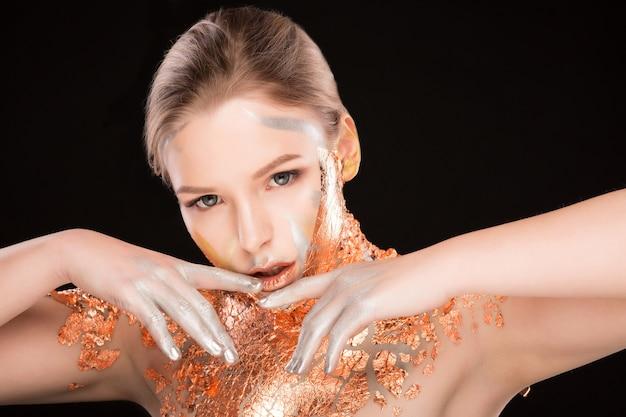 그녀의 어깨와 얼굴에 황금빛 호일이 있는 매력적인 금발 모델의 스튜디오 초상화