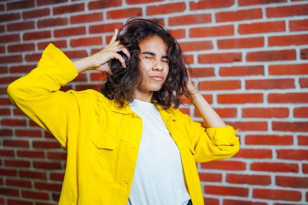 頭にヘッドフォンで、黄色のセーターを着ている不機嫌そうな若い女性のスタジオポートレート