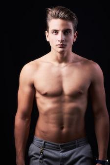 黒に分離されたハンサムな筋肉の上半身裸の若い男のスタジオポートレート