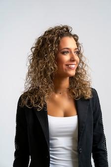 長い巻き毛のブロンドの髪を持つ幸せな陽気な若い女性のスタジオポートレート