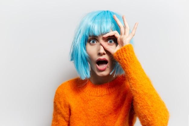 흰색 배경에 대해 확인 표시를 보여주는 행복 한 어린 소녀의 스튜디오 초상화. 주황색 스웨터와 파란색 가발을 착용.