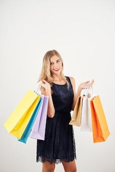 Студийный портрет радостной молодой женщины с хозяйственными сумками
