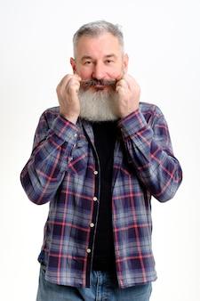 彼の口ひげを回転させるカジュアルな服を着た成熟したひげを生やした男のスタジオポートレート