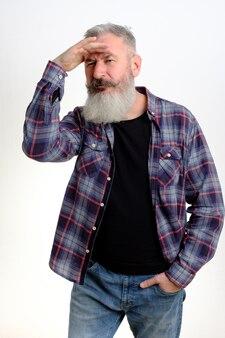 이마에 손을 넣고 옆으로 보이는 성숙한 수염 난 남자의 스튜디오 초상화