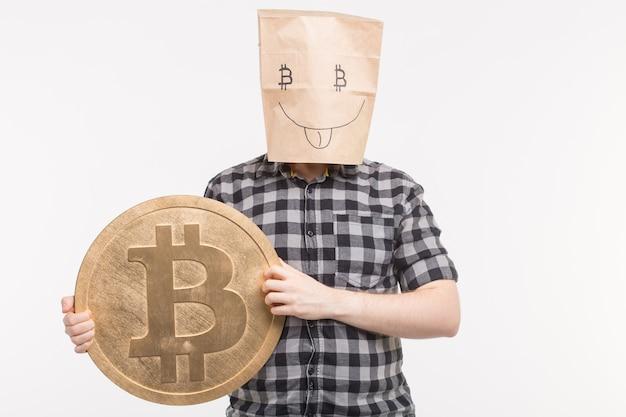 大きなビットコインで親指を示す幸せな紙のマスクの男性のスタジオポートレート