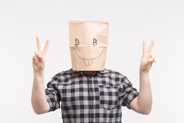 親指を立てて面白い紙のマスクを身に着けている男性のスタジオポートレート