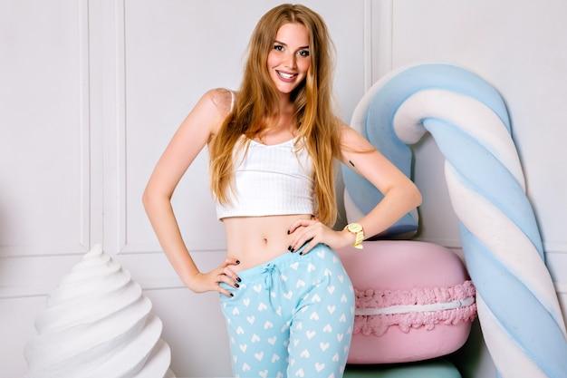 かわいいピジャマを着て、巨大なお菓子の近くでポーズをとるきれいなブロンドの女性のスタジオポートレート