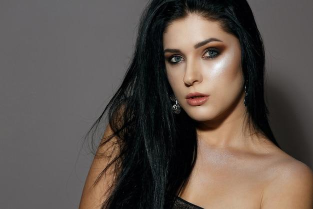 黒髪と茶色のスモーキーアイメイクと輝く肌を持つかなりブルネットの女性のスタジオポートレート。スタジオは灰色の背景の上で撮影しました。テキスト用のスペース