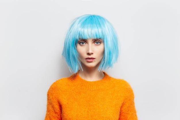 흰색 배경에 꽤 젊은 여자의 스튜디오 초상화. 주황색 스웨터와 파란색 가발을 착용.
