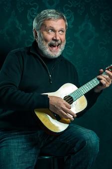 黒のスタジオで小さなギターを持つシニア男のスタジオポートレート