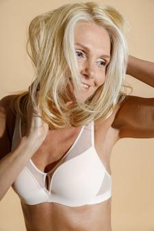 微笑んで調整する白いランジェリーで官能的な白人の成熟したブロンドの女性モデルのスタジオポートレート