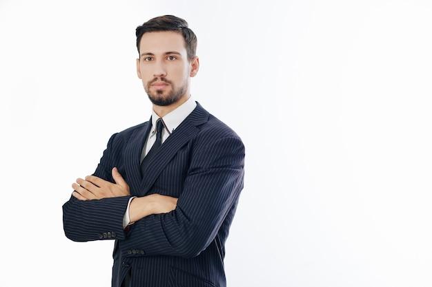 腕を組んで真面目な若いハンサムな自信を持って起業家のスタジオポートレート