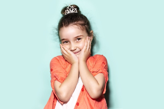 수줍은 어린 아이 소녀의 스튜디오 초상화, 뺨에 손바닥을 들고