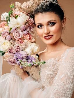 ブライダルブーケとウェディングドレスで笑顔のブルネットの花嫁のスタジオポートレート。